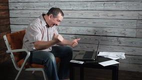 O homem louco das pessoas de cinquenta anos verifica a conta em linha e comemora o vencimento em seu laptop video estoque