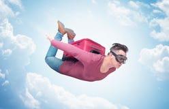 O homem louco nos óculos de proteção com a mala de viagem vermelha em seu voo traseiro para descansar o conceito é mais rápido em fotos de stock