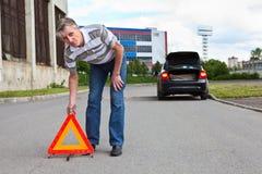 O homem maduro ajusta o sinal de aviso do triângulo Imagem de Stock Royalty Free