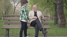 O homem maduro calvo que senta-se no parque no banco que l? um livro Um rapaz pequeno vem-lhe, o vov? toma vídeos de arquivo