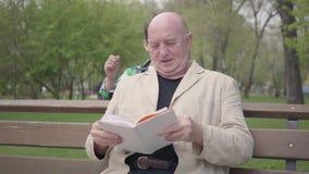 O homem maduro calvo que senta-se no parque no banco que l? um livro Rapaz pequeno que aproxima-se das m?os de tr?s e pondo vídeos de arquivo