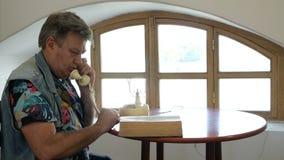 O homem maduro considerável senta-se na tabela e nos rolos através do livro velho grosso vídeos de arquivo
