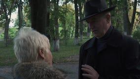 O homem maduro está dizendo a história à senhora no parque filme