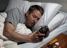 O homem maduro não pode cair tempo assim de vista adormecido no cloc do alarme fotografia de stock royalty free