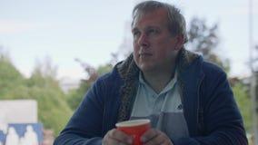 O homem maduro sério senta-se na tabela e nos olhares que pensa de lado sobre algo filme