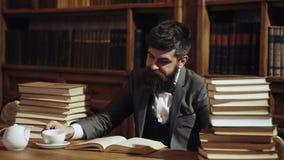 O homem maduro tem a cara cansado e olha sobrecarregado O homem senta-se na tabela com muitos livros O indiv?duo ? sobrecarregado video estoque