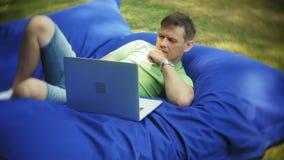 O homem maduro usa um portátil, encontrando-se em uma área da sala de estar do parque em sopros macios vídeos de arquivo