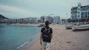 O homem magro está andando sobre a praia da estância citadina pequena em nivelar o tempo, opinião da parte traseira filme