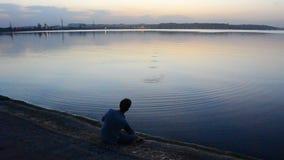 O homem magro novo joga pedras na água na noite video estoque