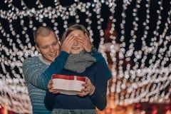 O homem mantiver seus olhos da amiga cobertos quando ela que dá um presente fotos de stock royalty free