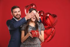 O homem mantiver seus olhos da amiga cobertos quando ela que dá um presente, surpresa romântica para o dia de Valentim fotos de stock