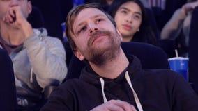 O homem mastiga a pipoca no cinema fotos de stock