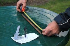 O homem mede o comprimento da haste de metal com roleta Foto de Stock