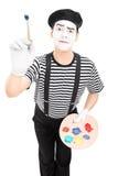 O homem mimica o artista que guarda um pincel Fotos de Stock Royalty Free