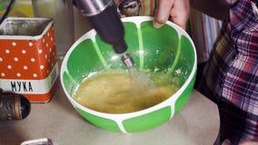O homem mistura ovos rápidos na bacia verde grande usando o misturador elétrico video estoque
