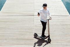 O homem moderno vestiu a camisa branca e calças pretas usando seu telefone ao estar em um cais de madeira com 'trotinette' elétri fotografia de stock