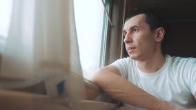 O homem monta a estrada de ferro do trem olha para fora a janela Curso da viagem da estrada de ferro do estilo de vida do trem do vídeos de arquivo