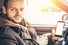 O homem mostra o dedo na zombaria do branco acima da tela do telefone que senta-se no carro fotos de stock