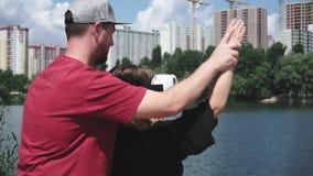 O homem mostra a fêmea como usar vidros de VR video estoque
