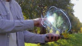 O homem mostra o holograma com planta video estoque