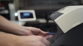 O homem muda o cartucho na impressora video estoque