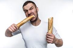 O homem muito com fome é esfomeado Quebrou uma parte longa de baguette em duas partes Está comendo um deste remenda Ele fotografia de stock