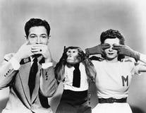 O homem, a mulher e um macaco que descreve não veem nenhum mal, não falam nenhum mal, não ouvem nenhum mal (todas as pessoas desc Imagens de Stock