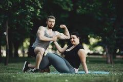 O homem muscular e a mulher obeso na rua malham imagem de stock royalty free