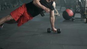 O homem muscular está fazendo o exercício da flexão de braço com peso em um exercício do crossfit movimento 4k lento video estoque