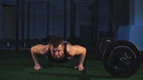 O homem muscular farpado veste o t-shirt preto pavimenta o exercício da flexão de braço no gym video estoque