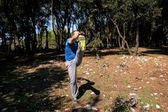 O homem muscular que faz o exercício está aquecendo-se pelo pé de aumentação acima no exercício de ar na floresta imagem de stock royalty free