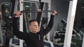 O homem muscular que faz o tr?ceps da corda do cabo abaixa o exerc?cio ao dar certo no gym filme