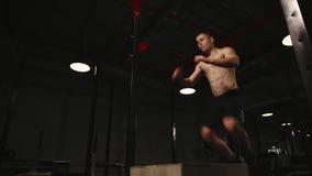 O homem muscular sem uma camisa executa saltos verticais em uma caixa de madeira Exercício aeróbio video estoque