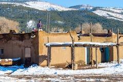 O homem não identificado trabalha com pá a neve do telhado de uma casa de adôbe no povoado indígeno de Taos, um pagamento do nati foto de stock royalty free