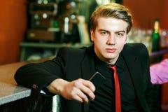 O homem na barra com um telefone em sua mão fotografia de stock royalty free