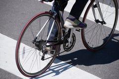 O homem na bicicleta cruza a rua no cruzamento pedestre foto de stock