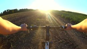 O homem na bicicleta está montando através do campo para encontrar o sol durante o nascer do sol do por do sol video estoque