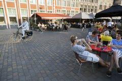 O homem na bicicleta passa o café exterior no centro medieval de ghent Imagens de Stock