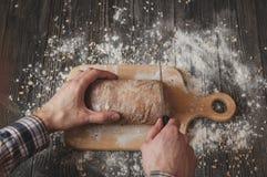 O homem na camisa de manta com faca cortou o pão caseiro na placa de madeira Imagem de Stock Royalty Free