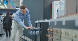O homem na camisa para abrir a porta de dispositivos da máquina de lavar louça na loja e a compará-la com outros modelos para com video estoque