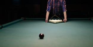O homem na camisa prepara-se para o jogo do começo do bilhar Fotografia de Stock Royalty Free
