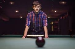 O homem na camisa prepara-se para o jogo do começo do bilhar Foto de Stock Royalty Free