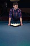O homem na camisa prepara-se para o jogo do começo do bilhar Imagem de Stock