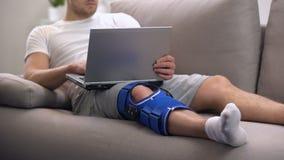 O homem na cinta de joelho da artrite que trabalha no portátil reabilita em casa o período e autônomo filme