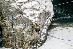 O homem na engrenagem do alpinismo que vem para baixo em uma corda ao Fotografia de Stock