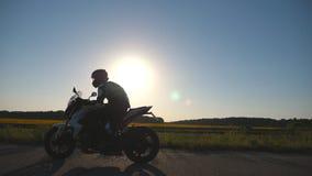 O homem na equitação do capacete em um velomotor na estrada com sol alarga-se no fundo Motociclista que conduz sua motocicleta so video estoque