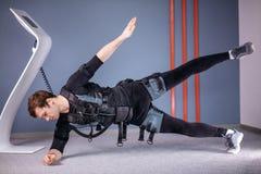 O homem na estimulação muscular elétrica sere fazer o exercício lateral da prancha ems imagem de stock