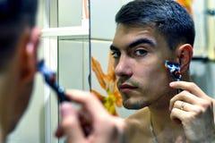 O homem na frente de um barbeador bonde seleto ou das lâminas clássico imagens de stock royalty free