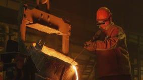 O homem na máscara mistura o metal derretido derramado da cubeta video estoque