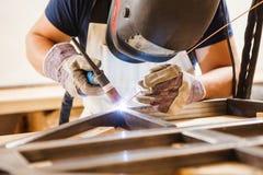 O homem na máscara protetora solda com soldadura do argônio-arco Fotografia de Stock